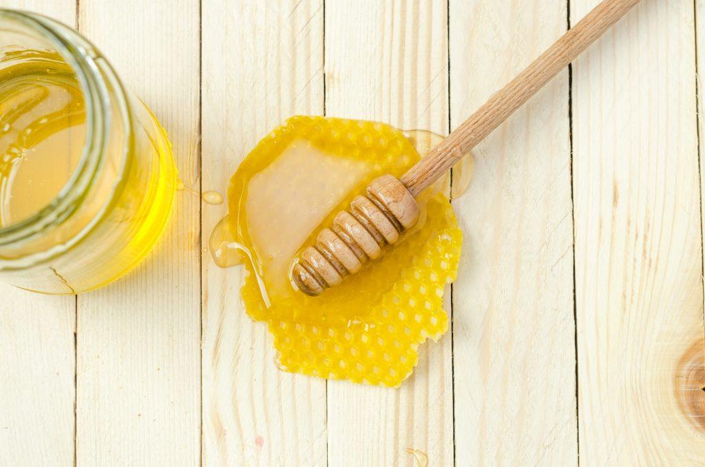 Em um fundo de madeira, há um pequeno favo de mel, com mel em cima e uma meleira de madeira. Ao lado, tem uma pequena jarra de mel.