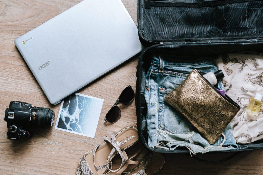 Foto de uma mala aberta, com algumas roupas e acessórios dentro. Ao lado, no chão, estão um notebook, câmera digital, óculos de sol, rasteirinha e uma foto Polaroid.