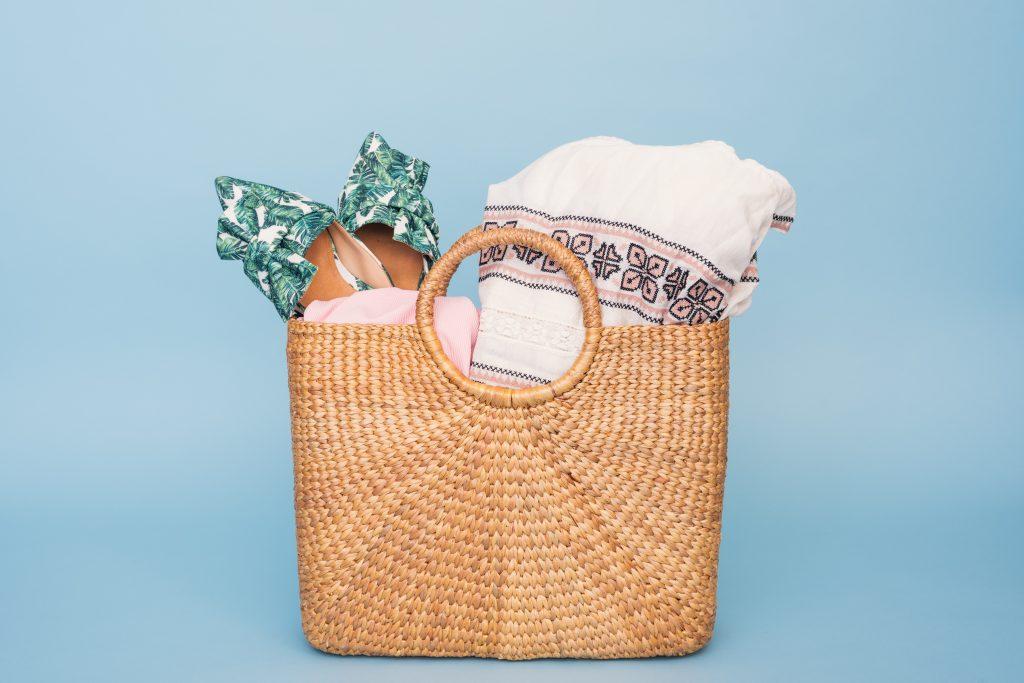 Imagem de fundo azul claro, com uma bolsa de palha no centro. Dentro da bolsa estão um par de sapatos estampados, uma toalha branca e uma canga rosa claro.