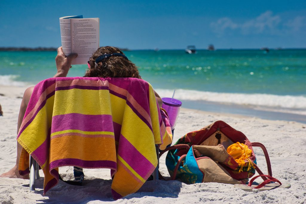 Mulher sentada em uma cadeira na praia, em cima de uma toalha colorida, lendo um livro e com um copo e água na mão. Ao lado dela no chão está uma bolsa de praia.