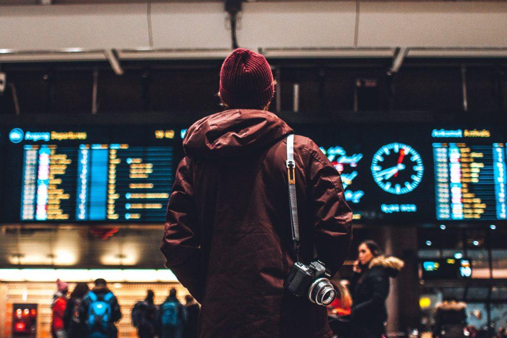 Foto de um rapaz de costas, com uma câmera à tiracolo, olhando para o painel de voos em um aeroporto.
