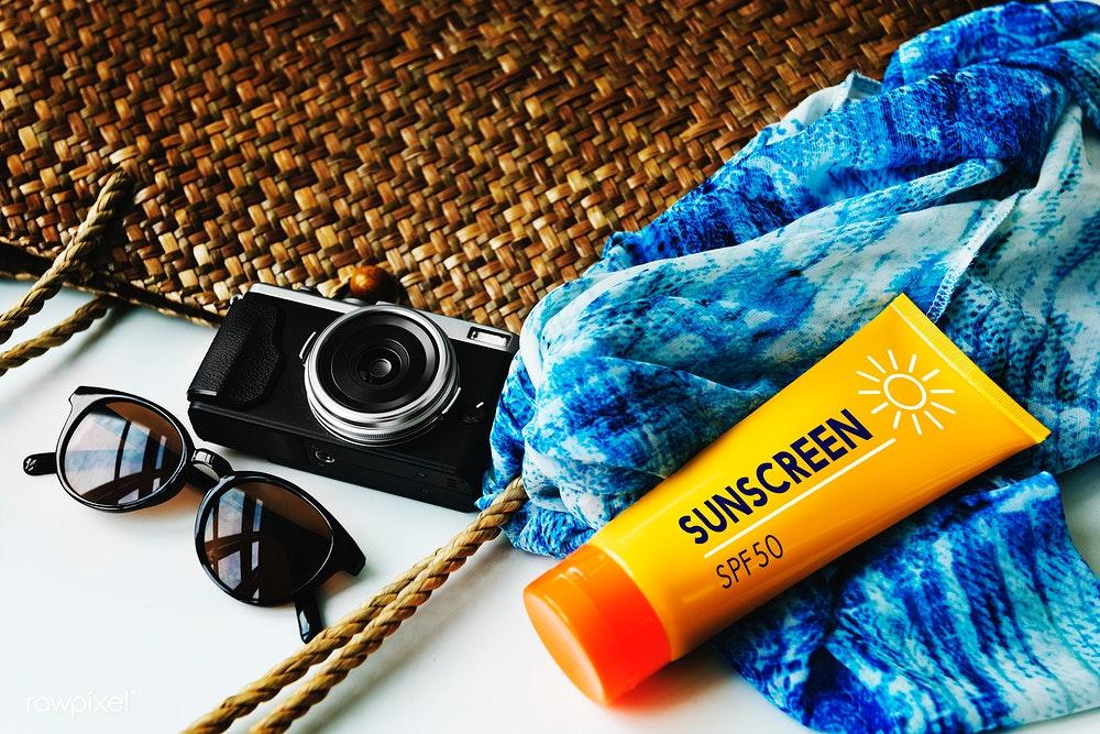 Foto de uma bolsa de palha trançada com um óculos de sol, câmera analógica, protetor solar e uma canga azul em cima.