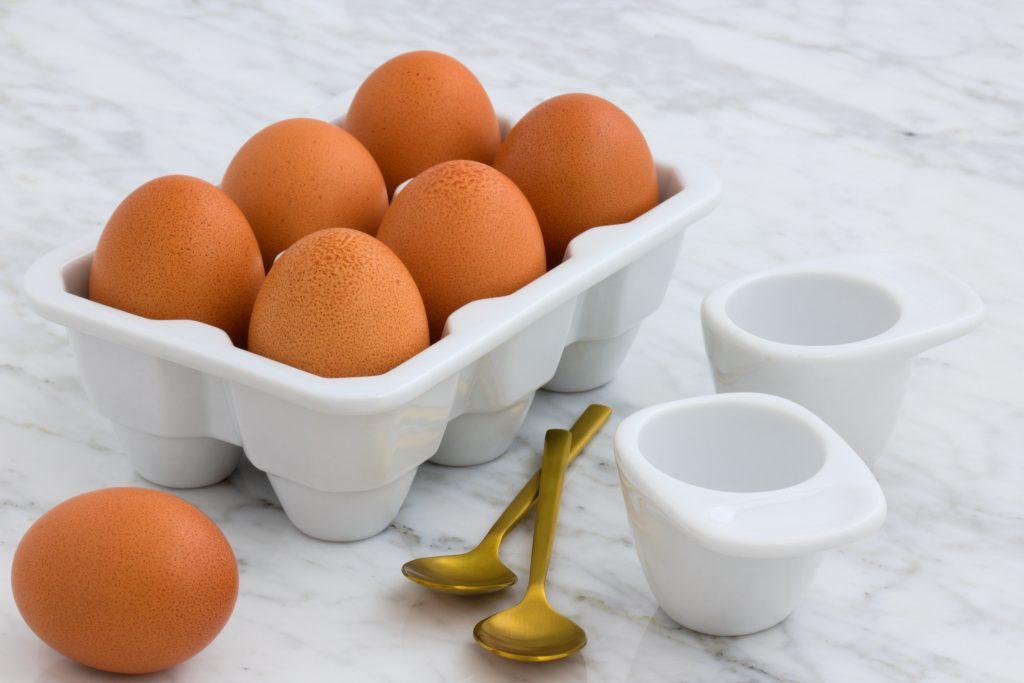 Uma caixinha branca com seis ovos e um para fora, ao lado duas colheres douradas.