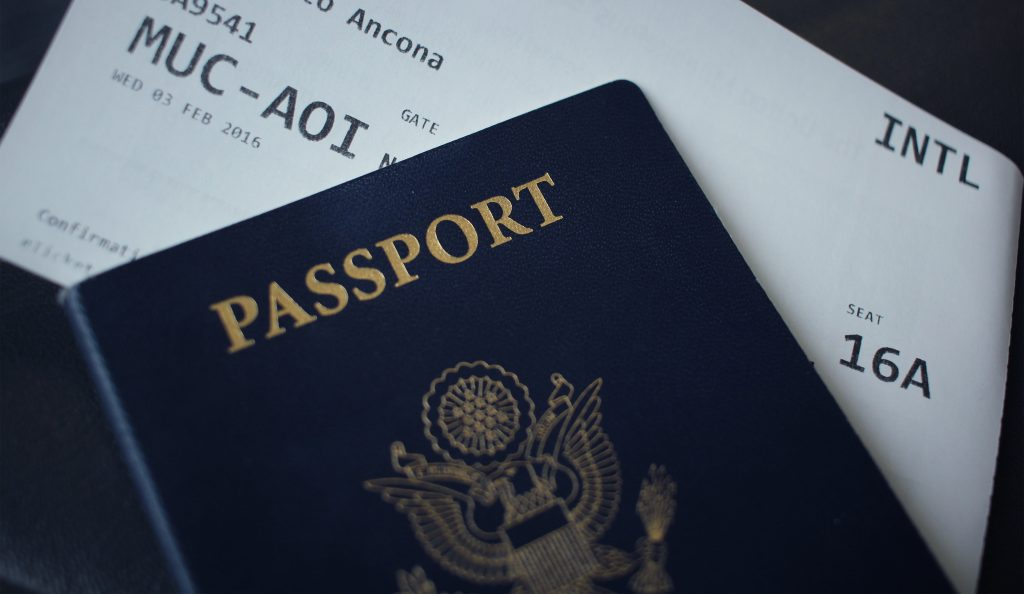 Foto de um passaporte e uma passagem aérea.