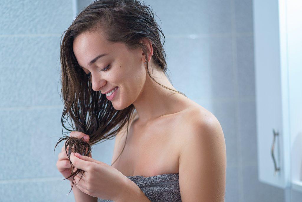 Em um banheiro, uma mulher morena usando uma toalha cinza está segurando os cabelos e olhando para eles.