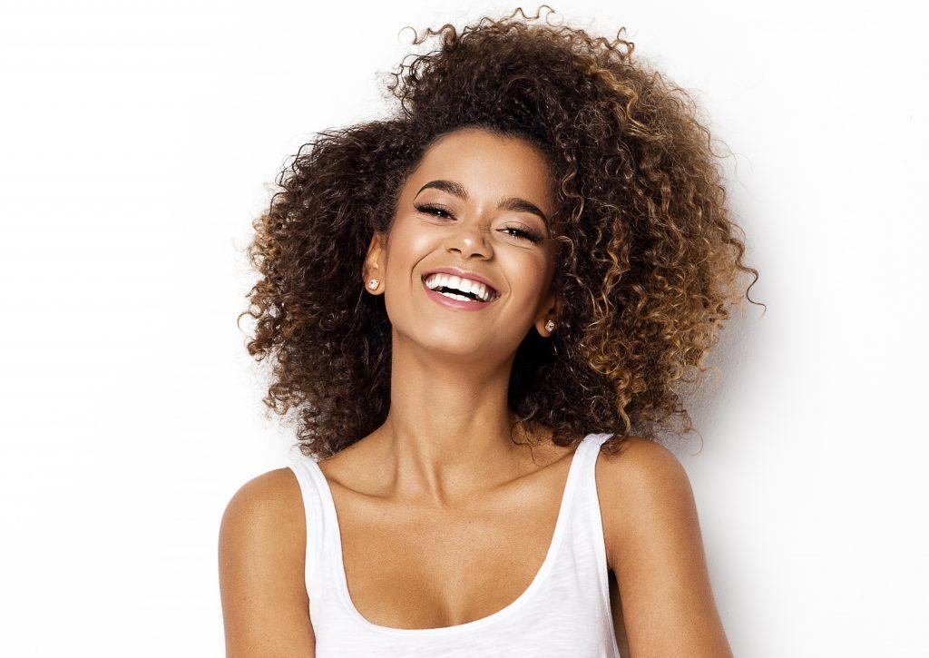 Mulher negra e cabelos cheios sorrindo porque aprendeu como hidratar o cabelo em casa.