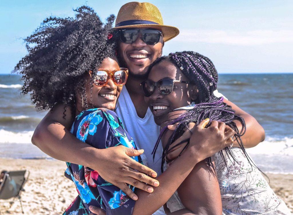 Foto de duas mulheres negras e um homem negro se abraçando e sorrindo na praia.