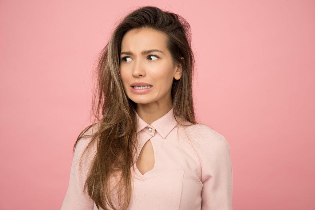 Mulher de cabelos castanhos claro e uma blusa rosa, olhando para o lado, com a boca ligeiramente aberta, com uma expressão de preocupação.