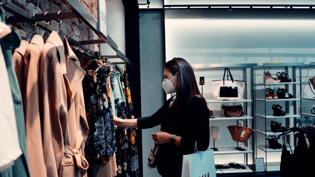 Mulher de cabelos lisos e escuros está de máscara de proteção em uma loja e vendo roupas em araras.