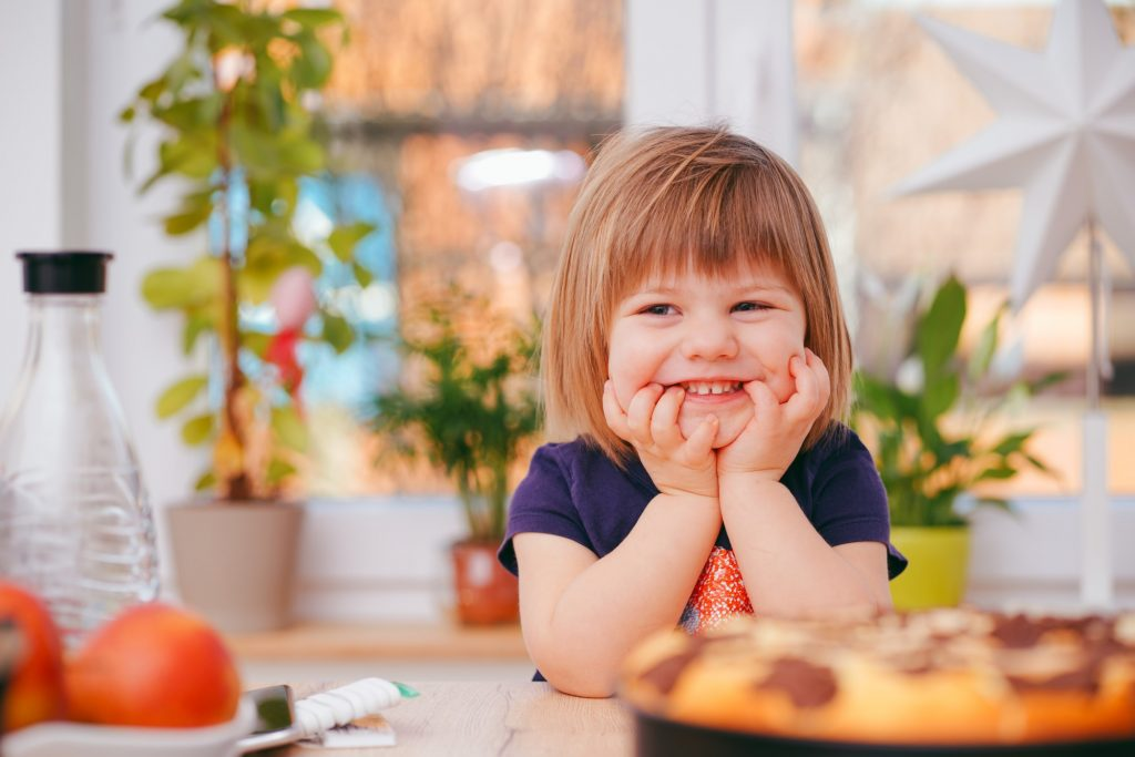 Foto de uma menina pequena loira de cabelo curto, ela está com uma camiseta azul escura e com as mãos no queixo, sorrindo. Ela está apoiada em uma mesa e em cima da mesa, desfocado, estão alguns pratos de comida.