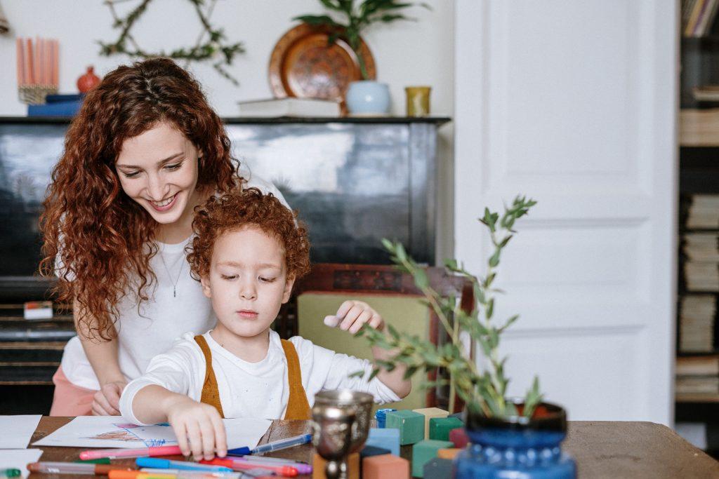 Mãe e filho estão em volta de uma mesa de madeira desenhando. Espalhado pela mesa tem várias canetas coloridas, papéis e um vaso de planta.