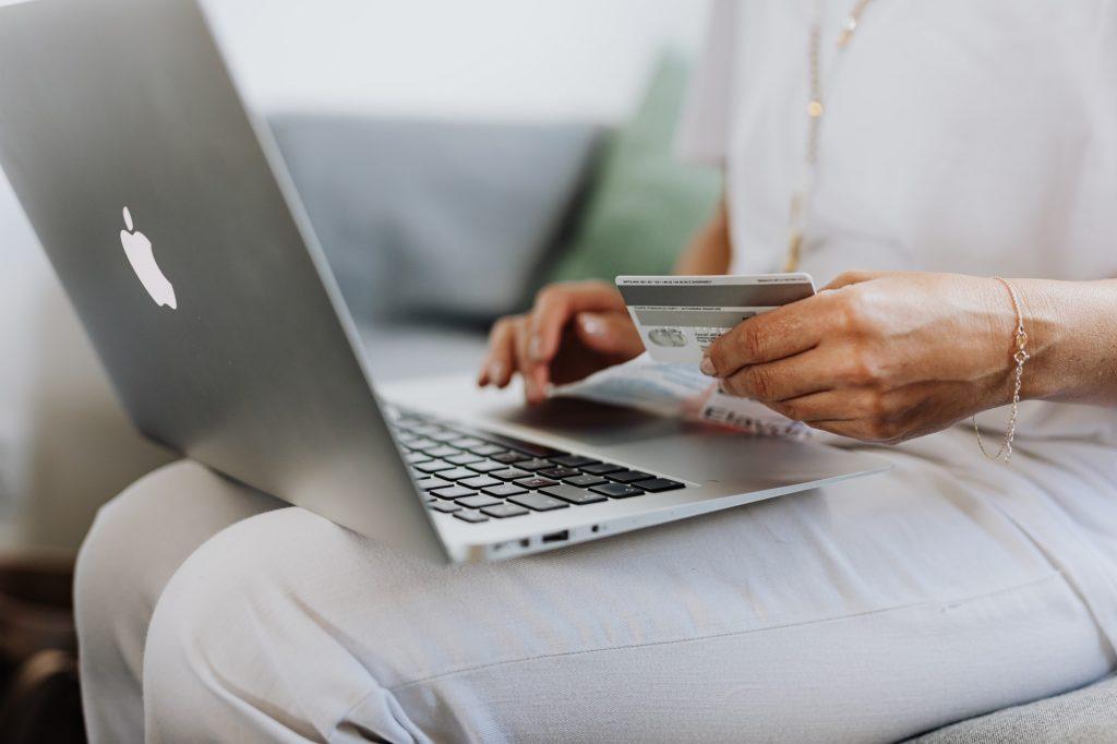 Uma mulher faz compras na Semana Brasil em seu notebook. A mulher está vestindo uma blusa e calça brancas e está sentada com o notebook no colo e digitando os números de um cartão que ela está segurando.