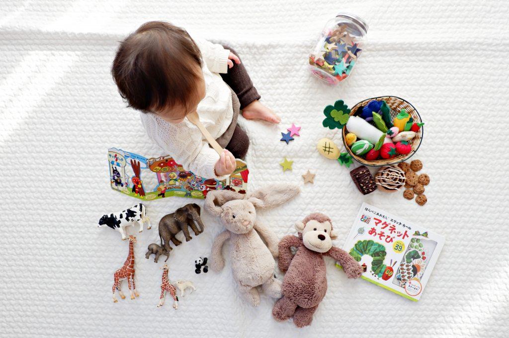 Foto de cima de uma criança pequena para ilustrar uma brincadeira educativa. Ela está em cima de um lençol branco e com vários brinquedos em volta, como duas pelúcias de animais, um livro, alguns alimentos de plástico e ela está brincando com uma colher de madeira.
