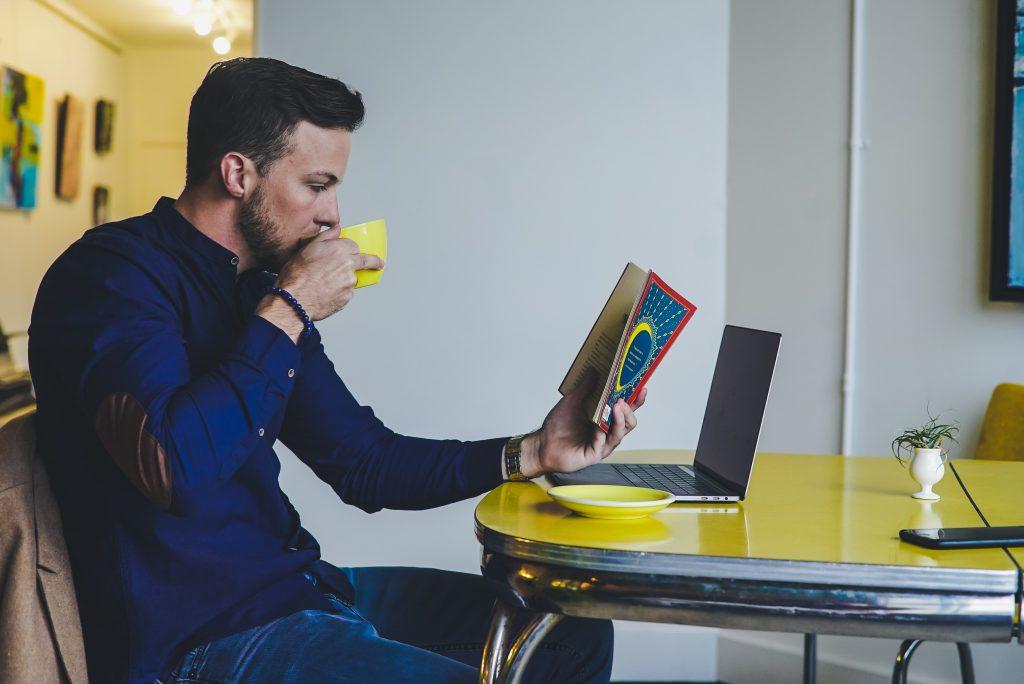 Homem vestindo uma camisa azul lê de uma assinatura de livros enquanto toma café em uma mesa.