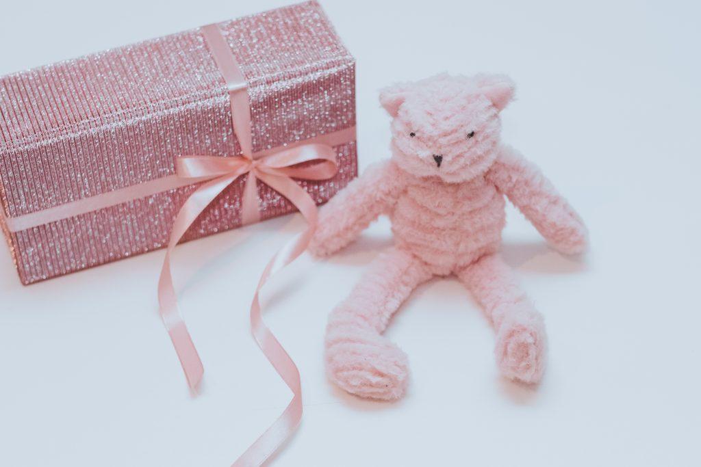 Uma caixa de presente rosa brilhante e ao lado, um ursinho rosa sentado para representar um presente por idade.
