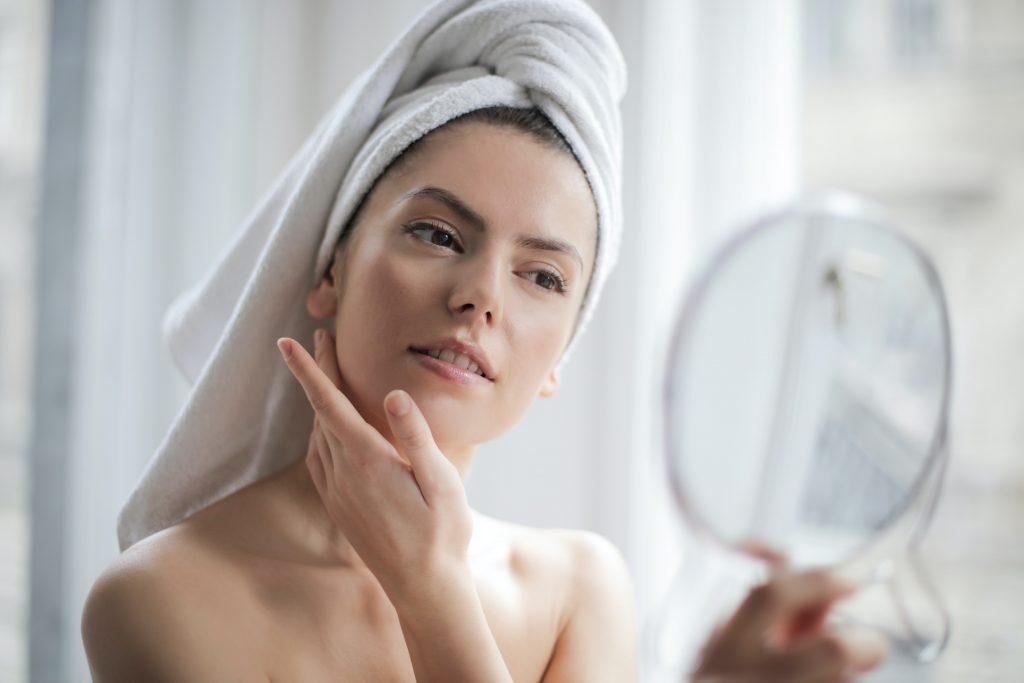 Mulher branca de toalha na cabeça e segurando um espelho, olhando para seu reflexo e tocando seu rosto.