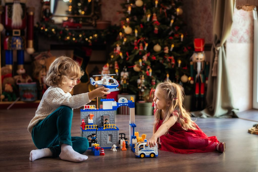 Duas crianças loiras brincando com uma estação policial de Lego.