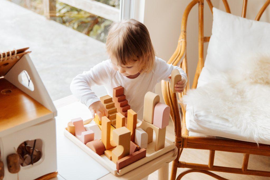 Menina pequena brinca com blocos de montar.