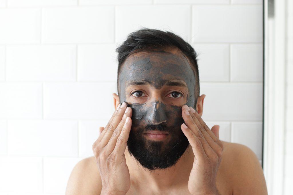 Homem está em frente ao espelho e em seu rosto ele usa uma máscara com um tipo de argila cinza.