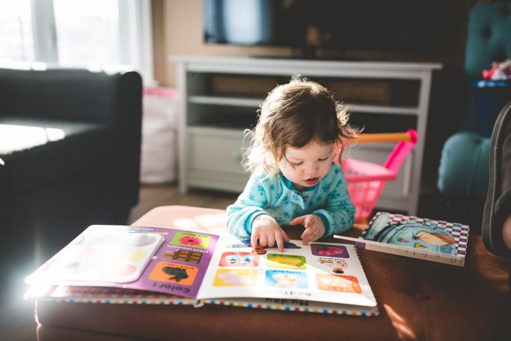 Uma garota pequena está usando uma blusa azul claro e lê um livro grande e roxo com várias imagens de uma assinatura de livros infantis.