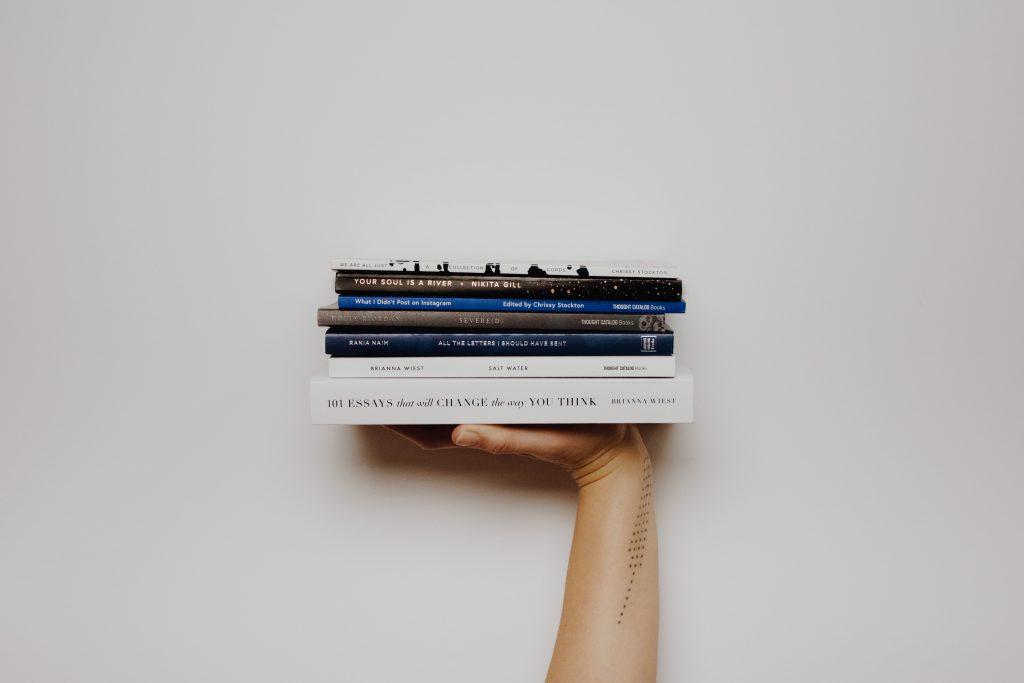 Em um fundo branco, uma mão segura seis livros de diferentes tamanhos e cores empilhados um sobre o outro.