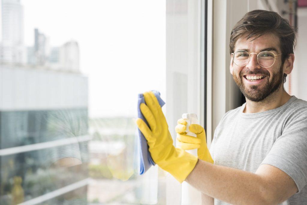 A imagem mostra um homem com um borrifador em uma das mãos. Na outra mão, ele segura um pano de microfibra e limpa o vidro.