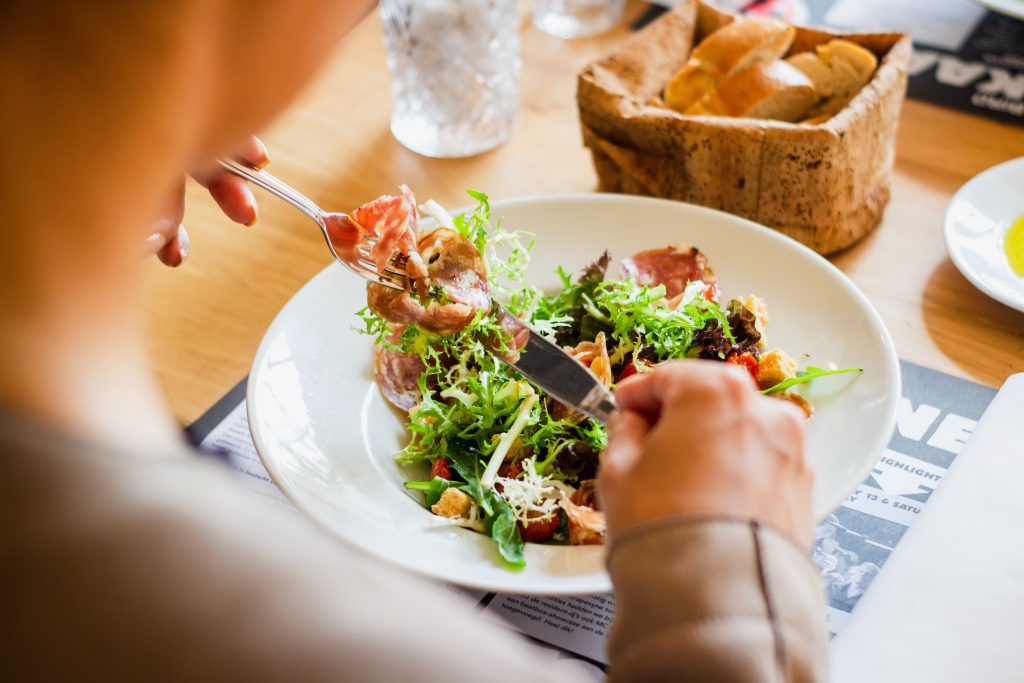A foto foi tirada por trás e mostra, desfocado, o pescoço de uma pessoa que está comendo um prato de salada em um restaurante.