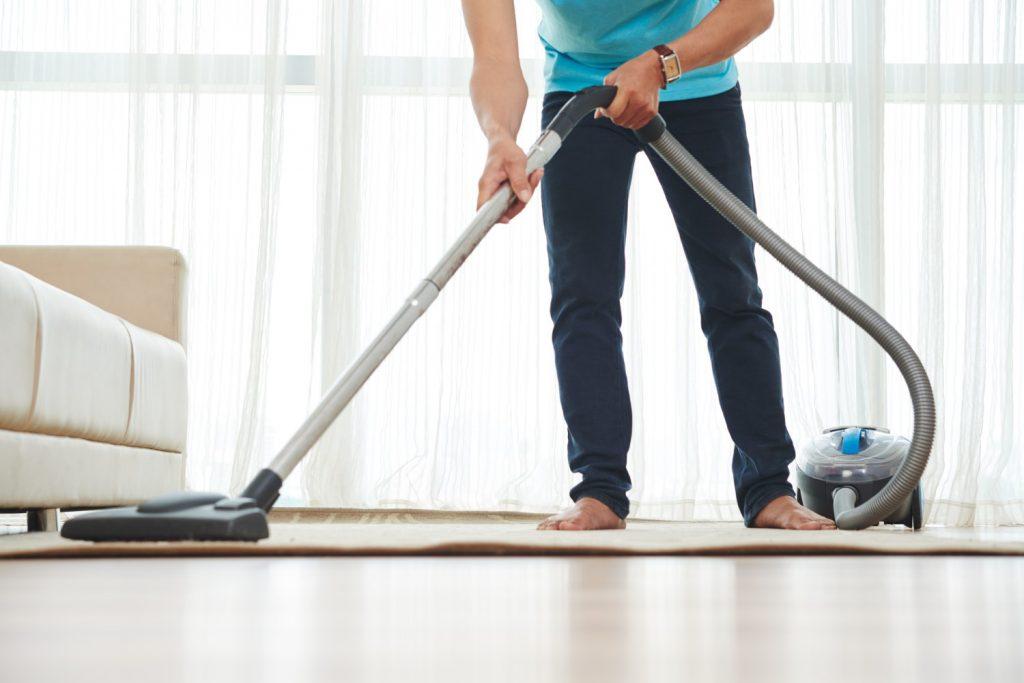 A imagem mostra um homem em pé em uma sala de estar. Ele está limpando um tapete com o aspirador de pó.