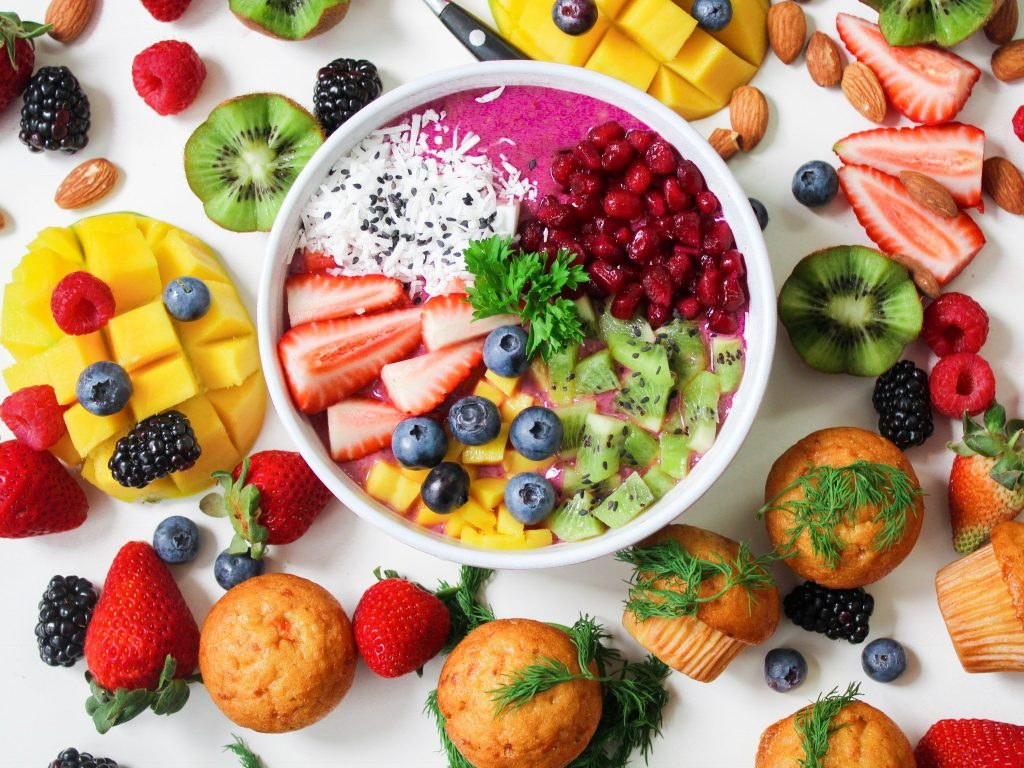 A imagem mostra uma mesa com diversas frutas saudáveis em uma mesa branca, como morango, manga, kiwi e ameixa. Ao centro da mesa, há um pote branco com um smoothie bowl de pitaya, coco ralado, kiwi, morango, manga e mirtilo.