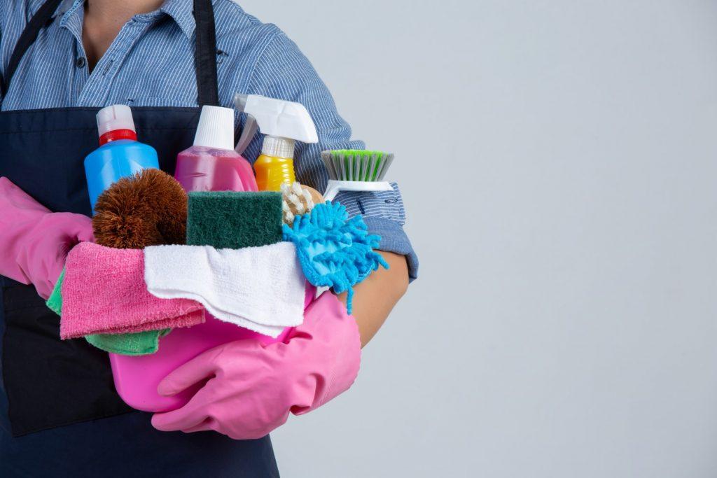 Dicas de faxina: A imagem mostra uma mulher de luvas de borracha rosa. Ela está segurando um balde que também é rosa. Dentro dele estão diversas embalagens de produtos de limpeza, alguns panos e esponjas para fazer faxina.